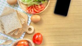 Preparazione casalinga della prima colazione del panino Il pane integrale è impilato su un tagliere di legno disposto su un tessu fotografie stock