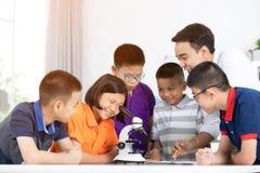 Preparazione d'esame asiatica del ragazzo e della ragazza sotto il microscopio Fotografia Stock