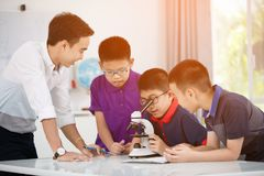 Preparazione d'esame del ragazzo asiatico sotto il microscopio Immagine Stock Libera da Diritti