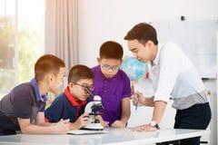 Preparazione d'esame del ragazzo asiatico sotto il microscopio Immagini Stock Libere da Diritti