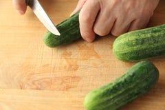 Preparazione dei cetrioli sul tagliere Immagine Stock