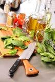 Preparazione dei fogli degli spinaci sulla scheda di taglio Fotografia Stock Libera da Diritti