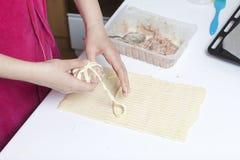 Preparazione dei glomeruli della carne Tacchino farcito, avvolto nelle strisce della pasta sfoglia Una donna avvolge una striscia Immagini Stock