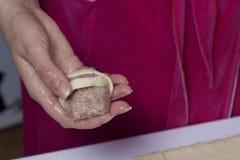 Preparazione dei glomeruli della carne Tacchino farcito, avvolto nelle strisce della pasta sfoglia Una donna sta tenendo una polp Immagine Stock Libera da Diritti