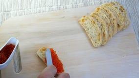 Preparazione dei panini con il caviale rosso Il caviale di color salmone rosso è spalmato di coltello da cucina su una fetta di p archivi video