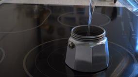 Preparazione del caffè con la macchinetta del caffè del geyser alla cucina privata stock footage