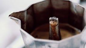 Preparazione del caffè con la macchinetta del caffè del geyser sulla cucina video d archivio