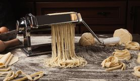Preparazione del fettuccine casalingo sulla macchina della pasta Immagini Stock Libere da Diritti