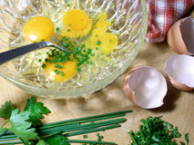 Preparazione del omlet con la erba cipollina ed il prezzemolo fotografie stock libere da diritti