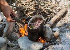 Preparazione del tè su fuoco di accampamento. Immagine Stock