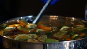 Preparazione dell'alcool caldo, vin brulé da vendere alla fiera paesana Glintwine da vino rosso con l'agrume e la menta in grande archivi video