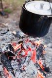 Preparazione dell'alimento su fuoco di accampamento Fotografia Stock