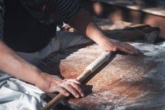 Preparazione della pasta con farina sulla tavola di legno di rotolamento della pasta immagini stock libere da diritti