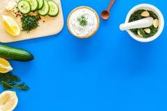 Preparazione della salsa greca del yogurt del cetriolo Lanci con yogurt vicino a pianta, il cetriolo, arance sul tagliere sul blu Fotografie Stock