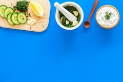 Preparazione della salsa greca del yogurt del cetriolo Lanci con yogurt vicino a pianta, il cetriolo, arance sul tagliere sul blu Immagine Stock Libera da Diritti