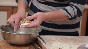 Preparazione delle patate ucraine casalinghe degli gnocchi che riempiono tagliando i pezzi rotondi di pasta Varenyky è un tipico stock footage