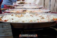 Preparazione di alimento collettivo La carne con la cipolla è fritta in padelle enormi che stanno in una fila Fotografia Stock Libera da Diritti