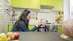 Preparazione di Halloween La mamma fa il trucco alla sua piccola figlia Sedendosi nella cucina video d archivio