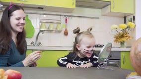 Preparazione di Halloween La mamma fa il trucco alla sua piccola figlia Sedendosi nella cucina stock footage