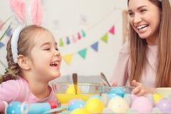 Preparazione di pasqua della figlia e della madre insieme a casa in orecchie del coniglietto che si siedono le uova di coloritura fotografia stock libera da diritti