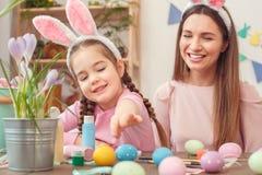 Preparazione di pasqua della figlia e della madre insieme a casa in orecchie del coniglietto che si siedono ragazza che prende uo fotografia stock libera da diritti