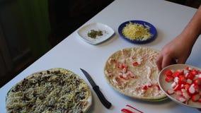 Preparazione di pizza L'uomo accatasta una miscela dei bastoni schiacciati del granchio sulla pizza Accanto alla tavola è una piz video d archivio