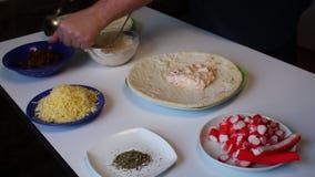 Preparazione di pizza L'uomo spalma una miscela di maionese e dei pomodori schiacciati sulla base per pizza Accanto alla tavola è video d archivio