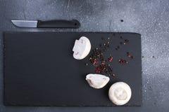 Preparazione di pranzo, dei funghi prataioli dei funghi, delle spezie e di un coltello su un bordo nero Copi lo spazio fotografie stock
