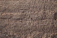 Preparazione di terra prima della piantatura La struttura della terra con le scanalature orizzontali dal rastrello, pronta ad att fotografia stock