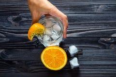 Preparazione di una bevanda di rinfresco con i cubetti di ghiaccio e gli agrumi fotografia stock