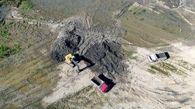 Preparazione di vista aerea per il carico del camion con la terra Trasporto di terra su un cantiere schiarimento stock footage