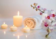 Preparazione per il bagno nel bianco con gli asciugamani, le candele e l'orchidea Immagini Stock