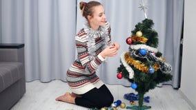 Preparazione per il Natale a casa: Giovane donna felice che decora i giocattoli d'attaccatura e sorridere di un albero di Natale  archivi video