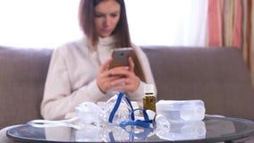 Preparazione per inalazione Nebulizzatore, maschera e medicina sulla tavola di vetro Donna con il telefono mobile video d archivio