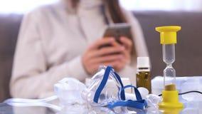 Preparazione per inalazione Nebulizzatore, maschera e medicina sulla tavola di vetro Donna di Unrecognazable con il telefono cell video d archivio