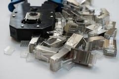 Preparazione per installazione della rete L'immagine mostra lo strumento di piegatura ed i connettori RJ-45 8P8C immagine stock