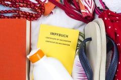 Preparazione per la festa, bagagli con swimwear, asciugamano, libro, suncream, Flip-flop, passaggio di vaccinazione immagine stock libera da diritti