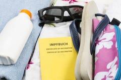 Preparazione per la festa, bagagli con swimwear, asciugamano, occhiali da sole, suncream, Flip-flop, passaggio di vaccinazione fotografia stock libera da diritti