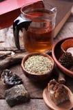 Preparazione sana della tisana con la teiera asiatica di vetro, candela dettagli di legno e di pietra e fondo di legno rustico d' fotografie stock