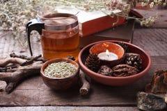 Preparazione sana della tisana con la teiera asiatica di vetro, candela dettagli di legno e di pietra e fondo di legno rustico d' fotografie stock libere da diritti