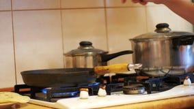 Preparazione trattata del pasto in una pentola sulla stufa in una cucina domestica archivi video