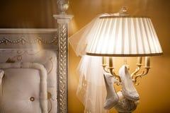Preparazioni per le nozze Scarpe bianche dal vestito da sposa che appende sulla lampada fotografia stock libera da diritti