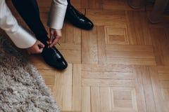 Prepare atar los zapatos, consiguiendo listos por la mañana en piso de madera imagenes de archivo
