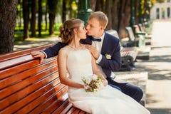 Prepare besar a la novia en parque en banco de madera imagen de archivo
