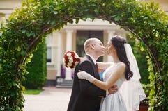 Prepare besar a su novia el día de boda cerca de arco fotos de archivo libres de regalías