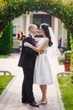 Prepare besar a su novia el día de boda cerca de arco fotografía de archivo