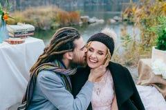 Prepare blando besar a su novia hermosa en mejilla Ceremonia de boda del otoño en estilo rústico al aire libre Los recienes casad fotografía de archivo libre de regalías