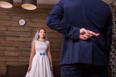 Prepare com cruzes que os dedos fazem a promessa à noiva imagens de stock royalty free