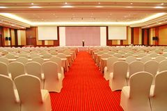 Prepare a conference room with the placement of the chairs style. Theater with chairs on the ground, the red carpet wearing a Skirt. The front side has shelves Royalty Free Stock Images