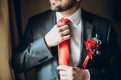 Prepare conseguir listo por la mañana, sosteniendo el lazo rojo día de boda pre fotos de archivo libres de regalías